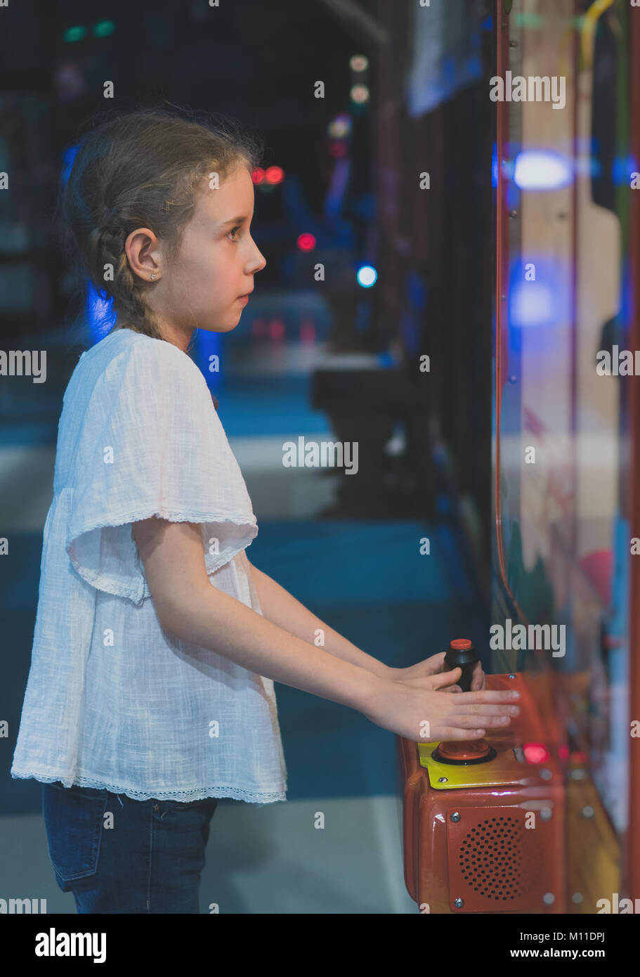 Little girl playing claw crane in theme park. - Stock Image