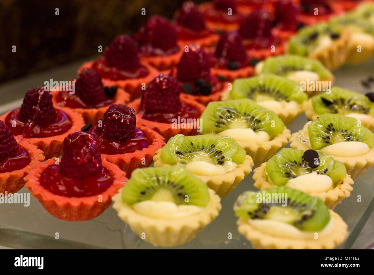 Dessert of raspberry and kiwi with cream and jelly in the crisp tartlets - Stock Image