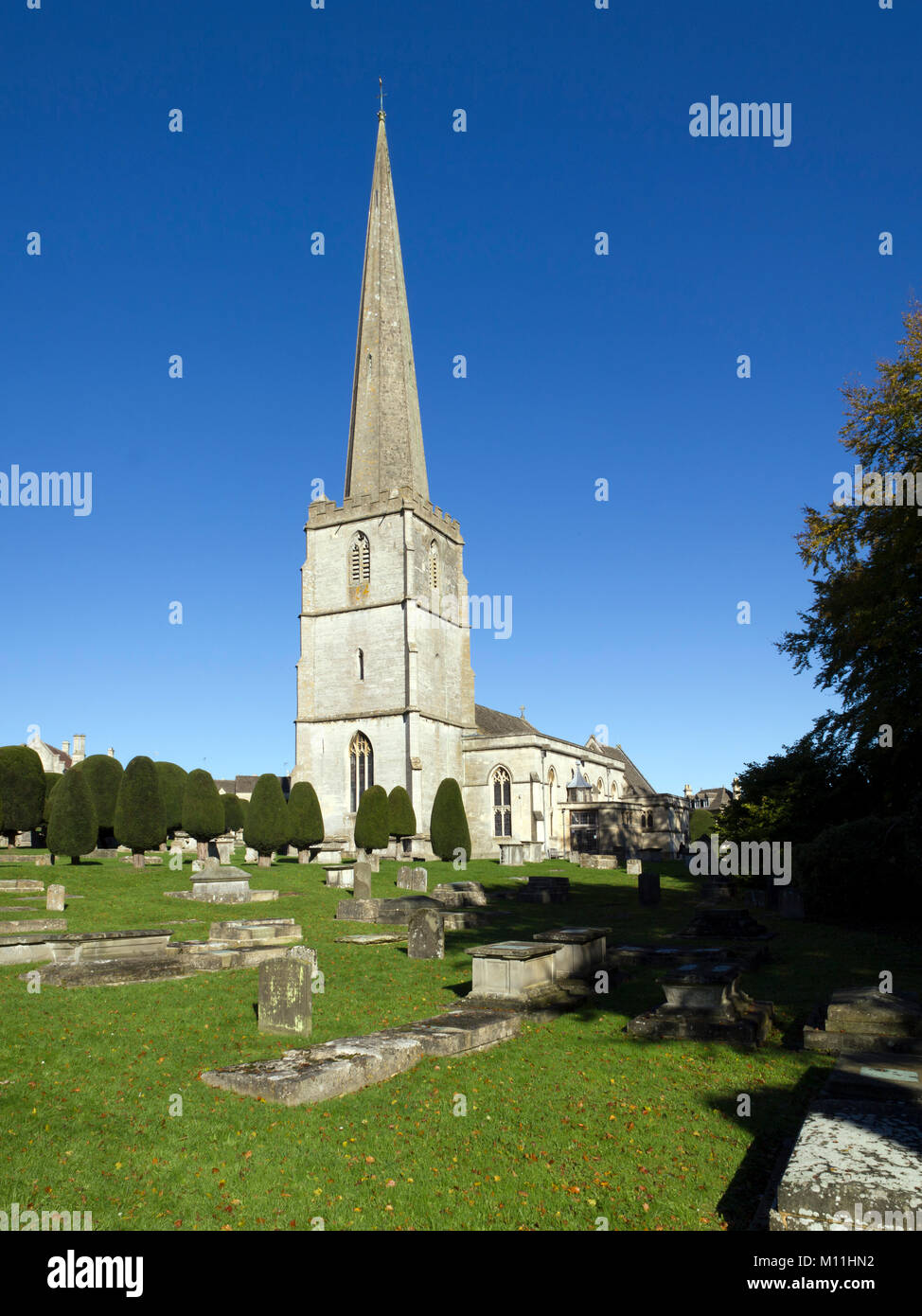 The historic church and churchyard yew trees at Painswick in the Cotswolds, Gloucestershire, UK. Wide-angle composite - Stock Image