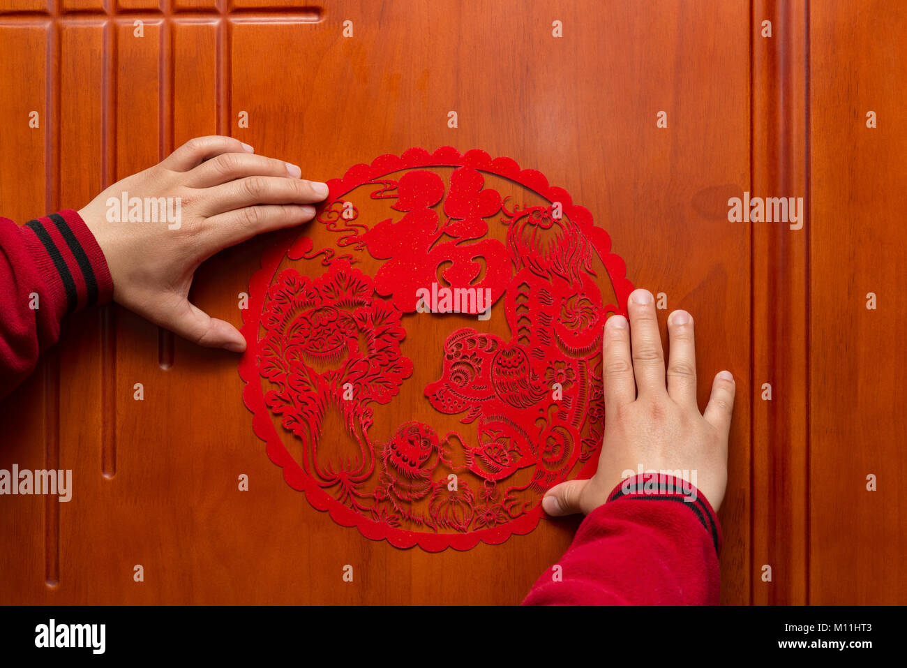 man sticking a Chinese New Year of the Dog 2018 to a door the Chinese means fortune and family - Stock Image