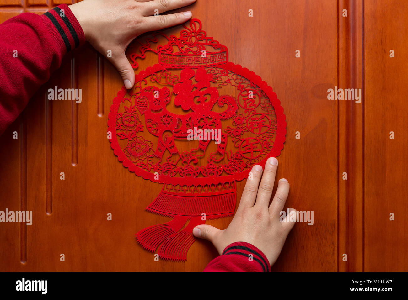 man sticking a Chinese New Year of the Dog 2018 to a door the Chinese means fortune and family Stock Photo