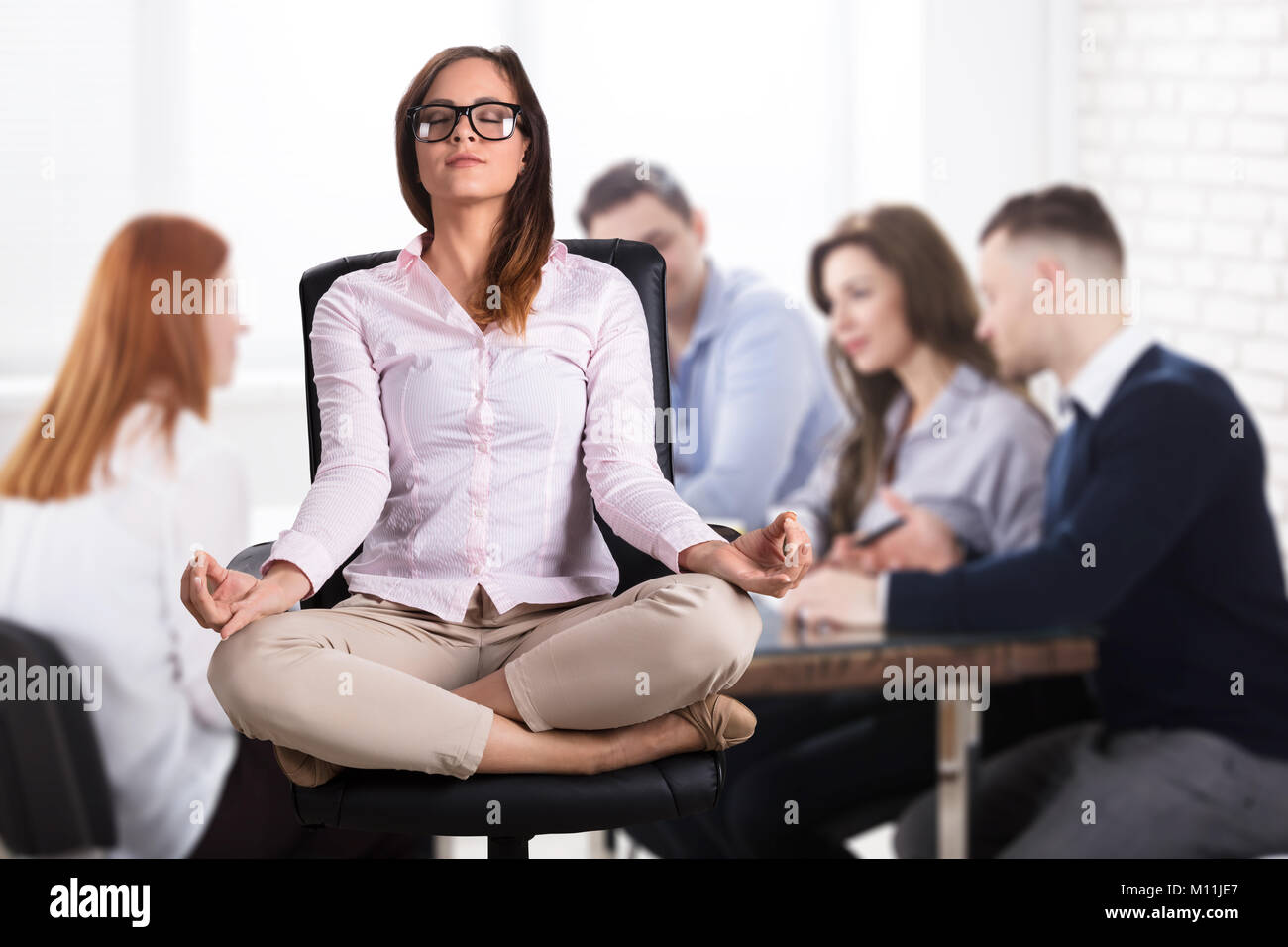 meditation office. Relaxed Businesswoman Sitting On Chair Doing Meditation In Office F