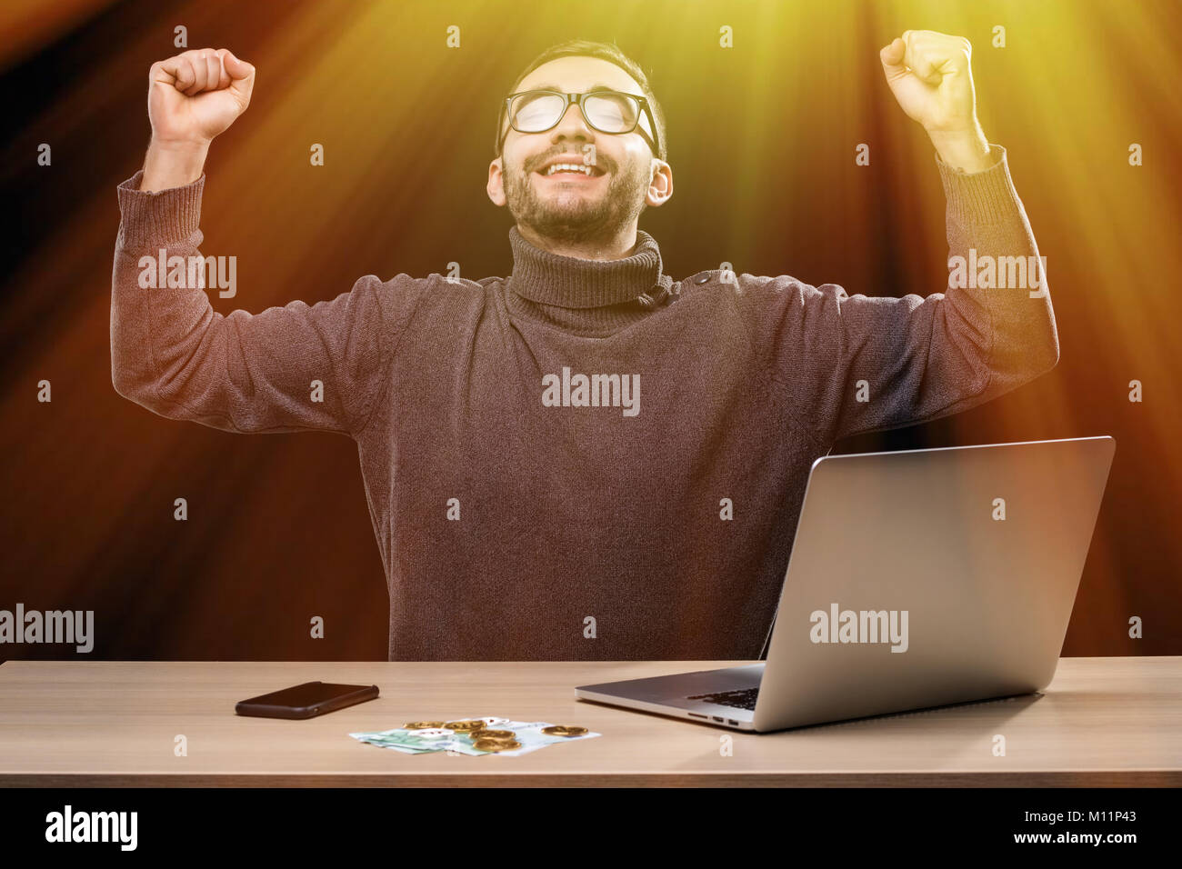 Triumphant office worker succeeded in striking a good deal online - Stock Image