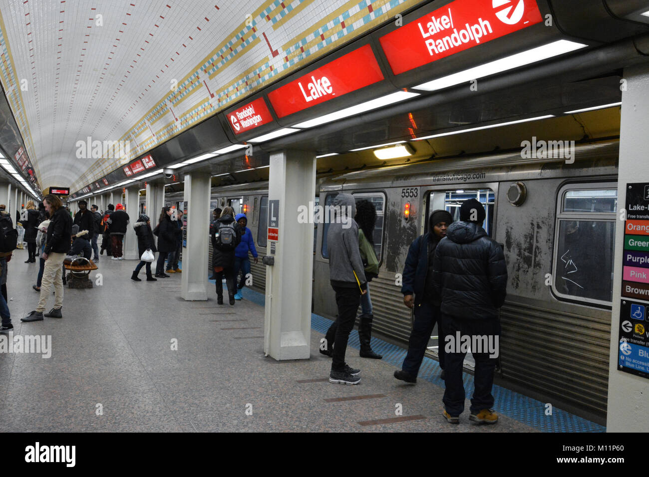 Passengers board a south bound Red Line train on the State Street Subway. The Lake St. stop provides easy access - Stock Image