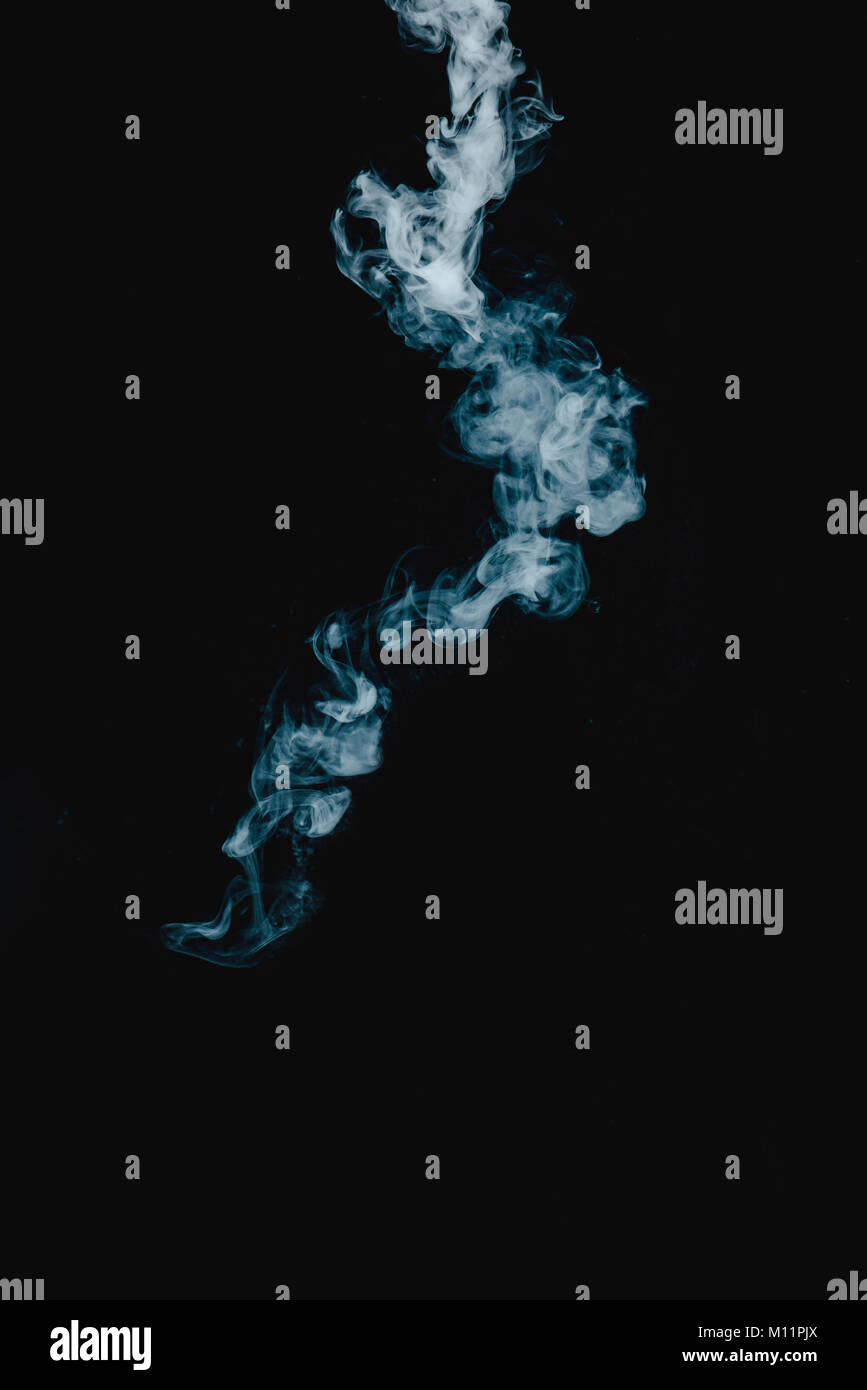 Vapor texture from a hot drink on a black background. Blue smoke with copy space. - Stock Image
