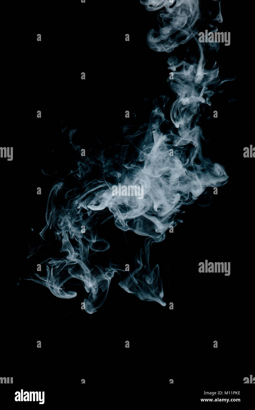 Steam texture from a hot drink on a black background. Blue smoke with copy space. - Stock Image
