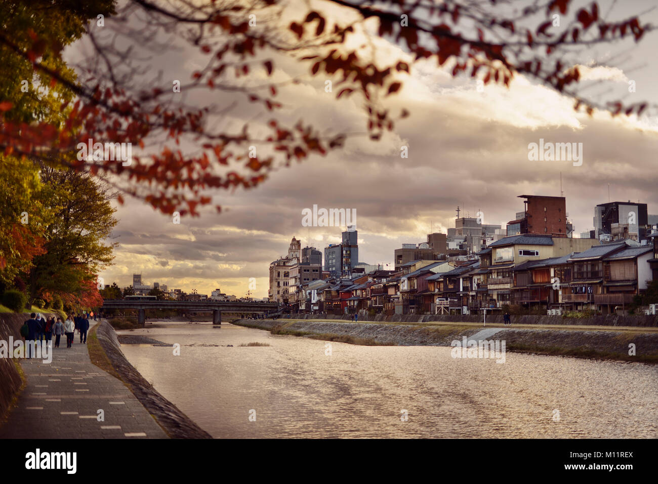 Pathways along Kamo River, Kamo-gawa, with Shijoo bridge in the background in a beautiful dramatic autumn sunset Stock Photo