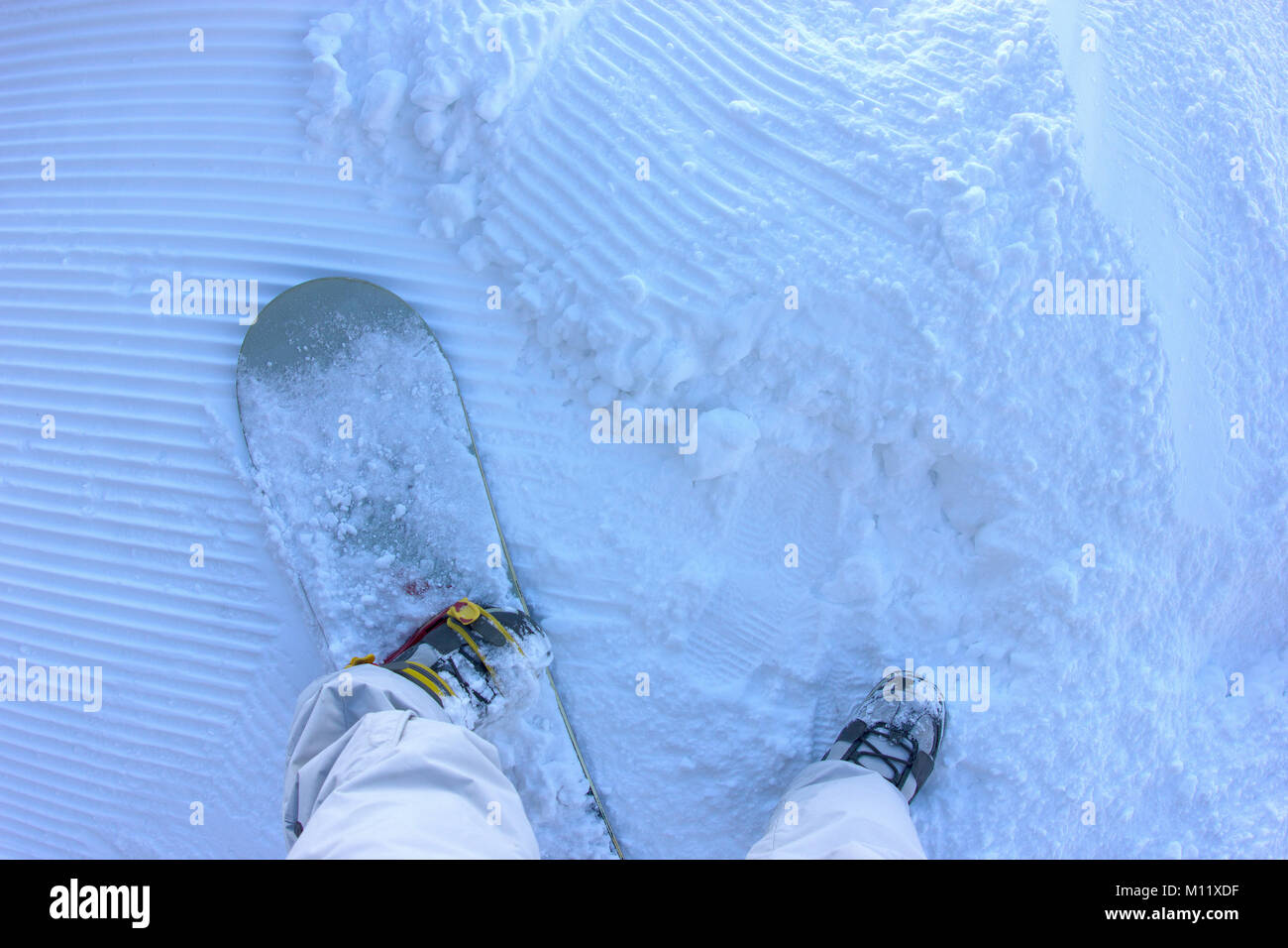an unusual shot of a snowboarder standing on the snow piste getting ready to ride - Stock Image