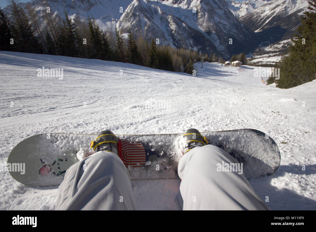 a view of the piste with snowboard in the foreground in the Italian Alps - Stock Image