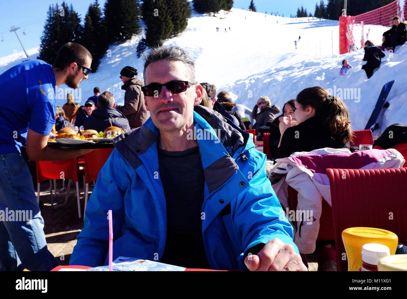 Eating in an outside ski resort restaurant on a sunny day, Samoens France - Stock Image