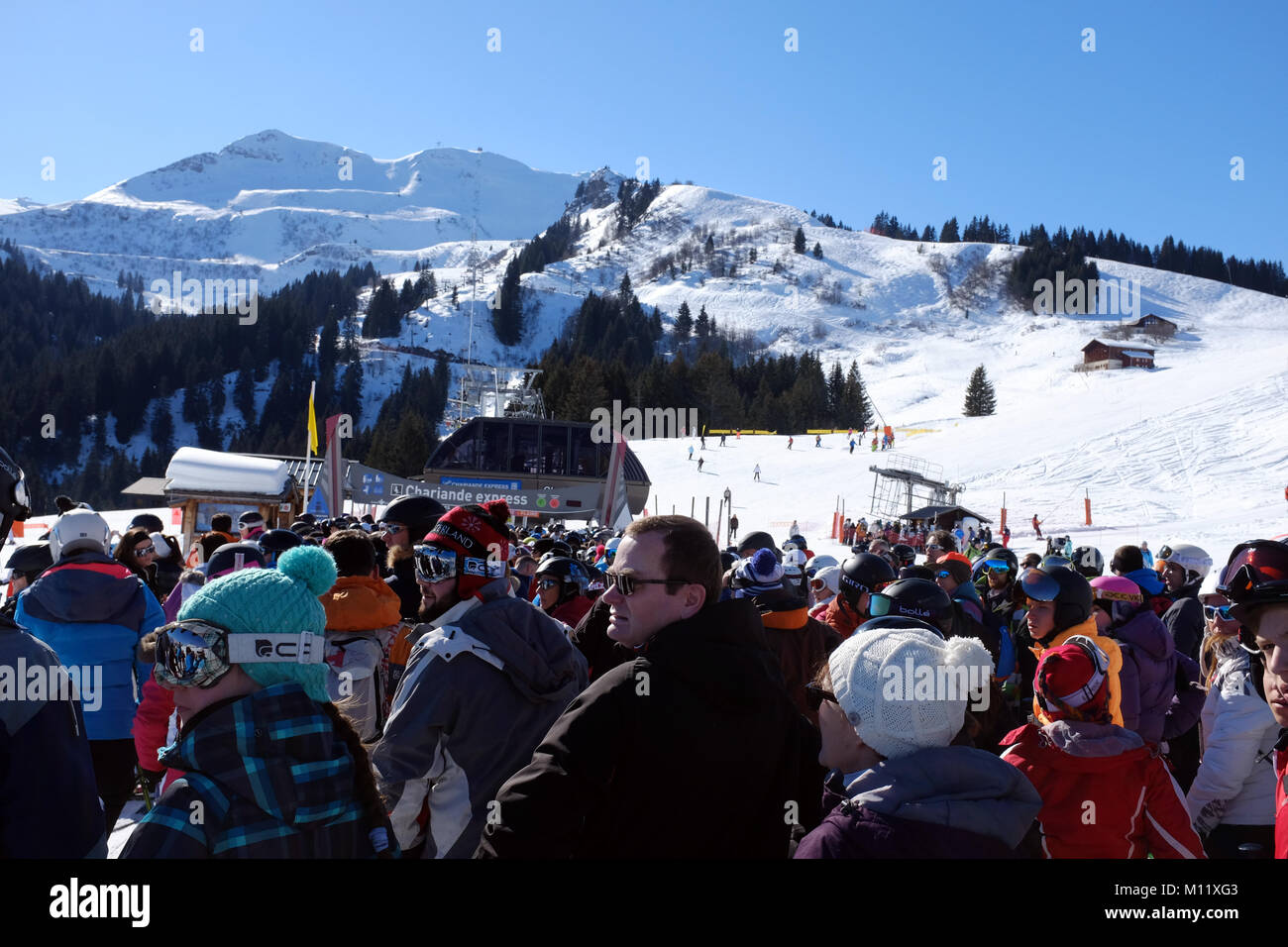 Queue for the skiing chair lift half term Samoens France - Stock Image