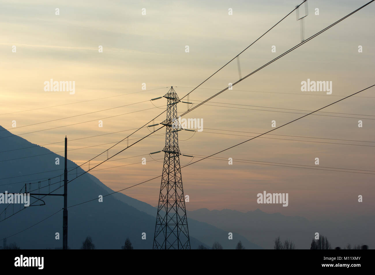 electricity poles and cables with mountains at sunset in the winter
