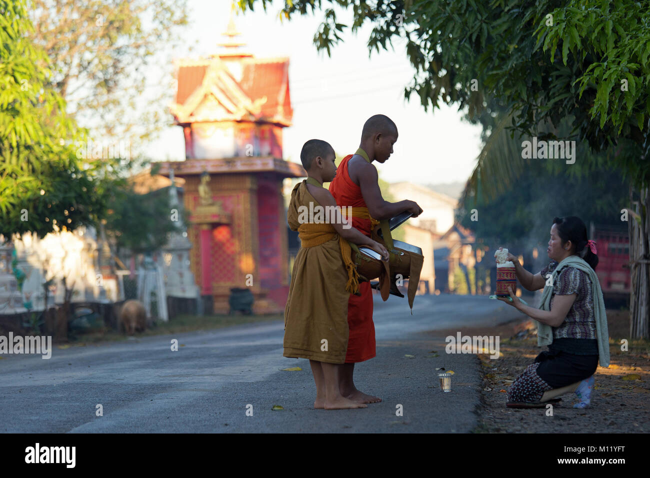 Young Monks bagging for their food in the early morning in Tad Lo Village - Southern Laos, Indochina - Stock Image