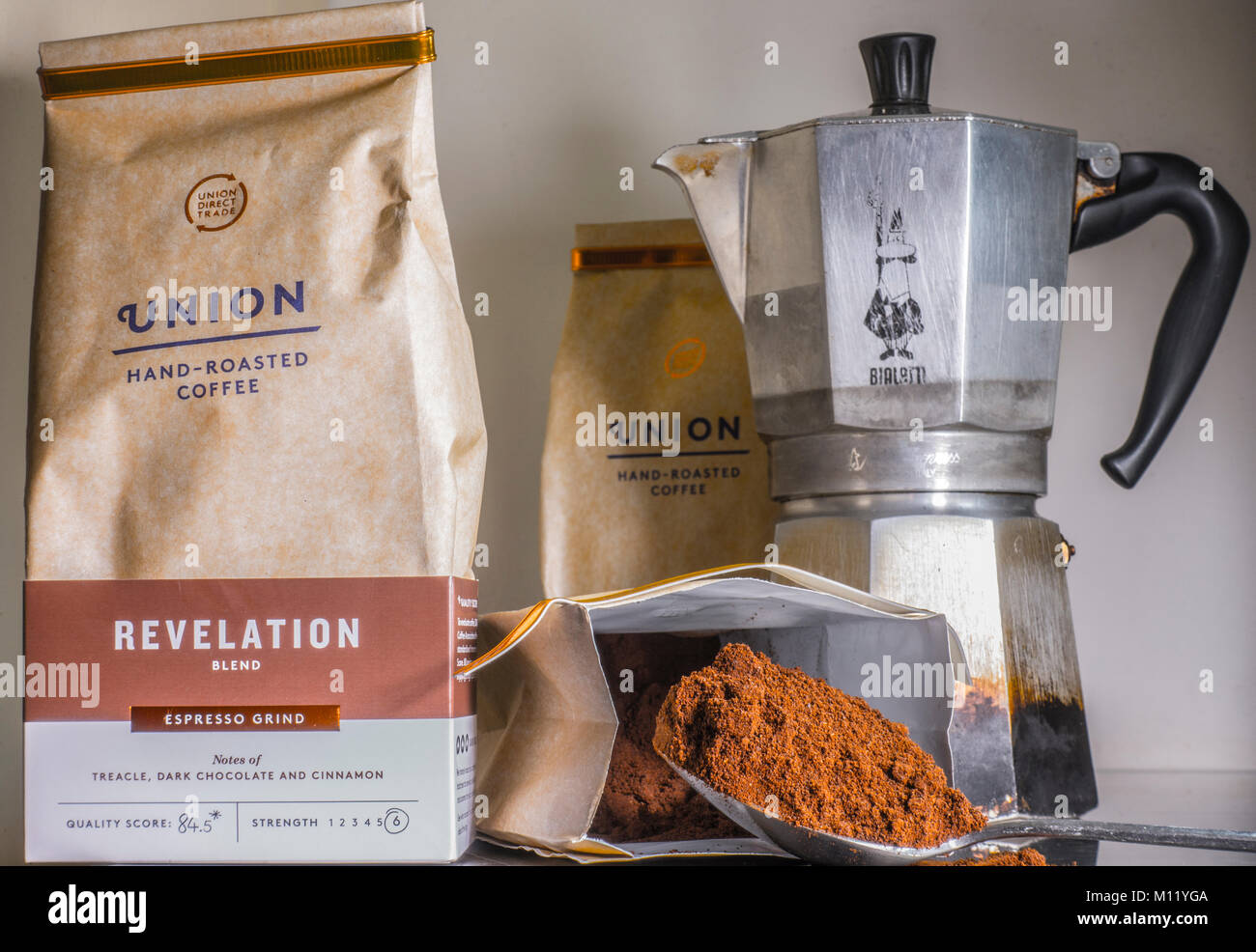 Spoonful of ground Arabica coffee, next to packs of Union hand-roasted, espresso grind, and a traditional Bialetti - Stock Image