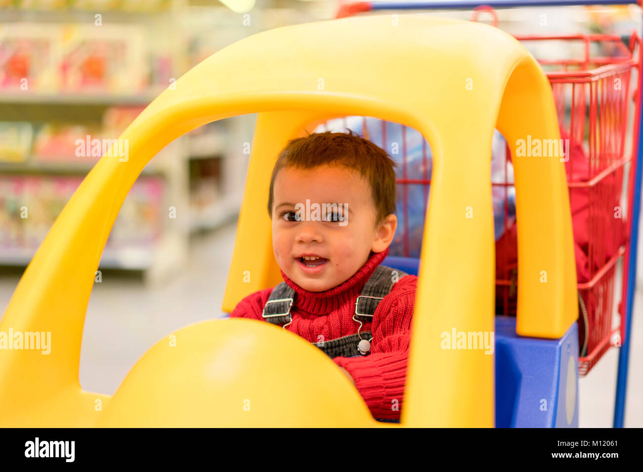 little cheerful boy in a trolley in a shopping center - Stock Image