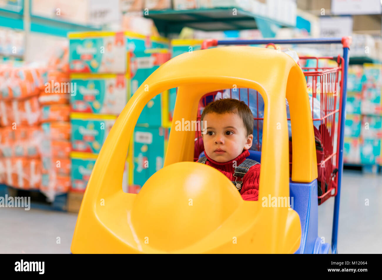 little cheerful boy in red sweater in a shopping cart in a shopping mall against a background of diapers - Stock Image