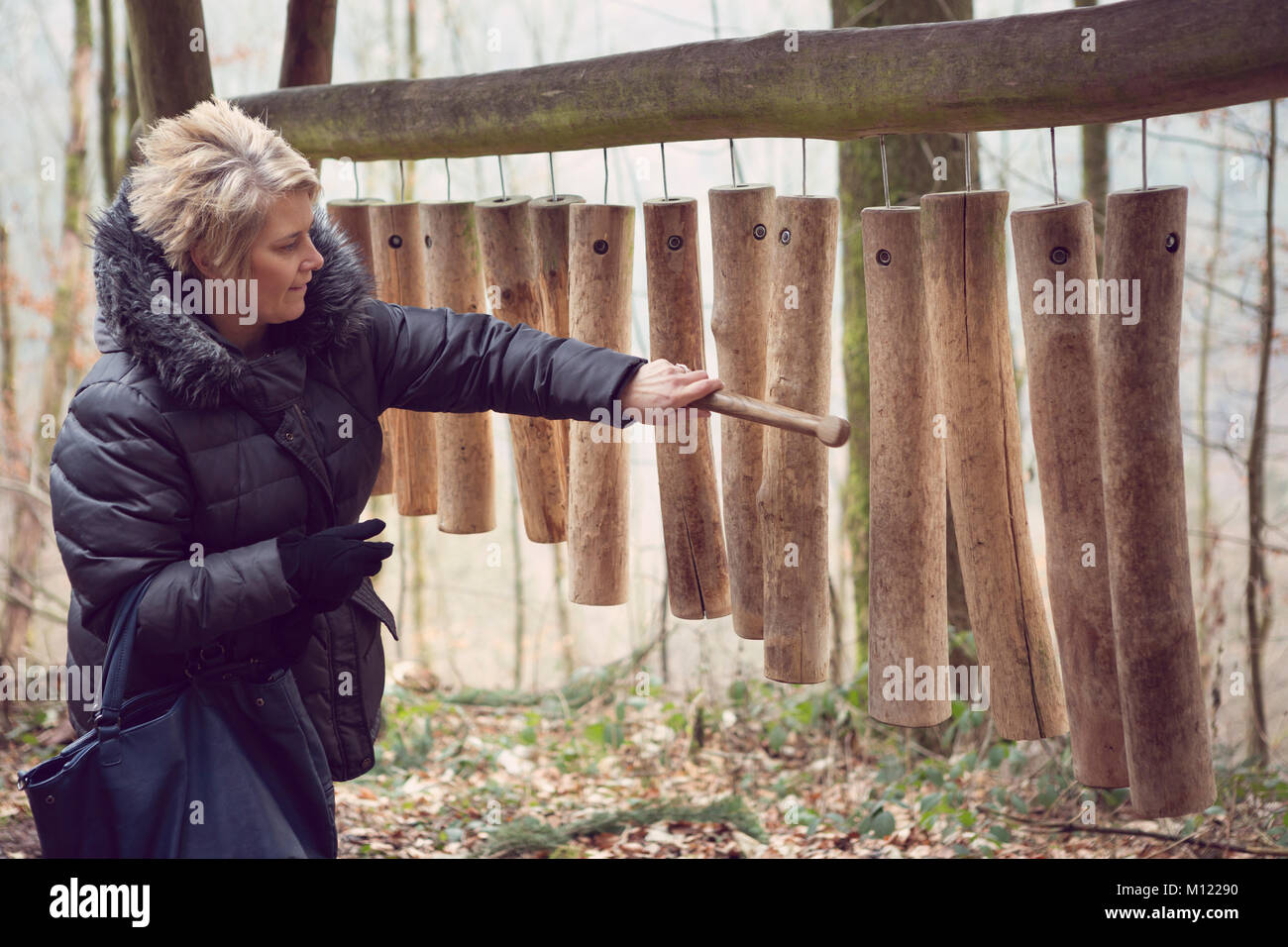 Adult female playing on a large wooden wind chime instrument - Stock Image