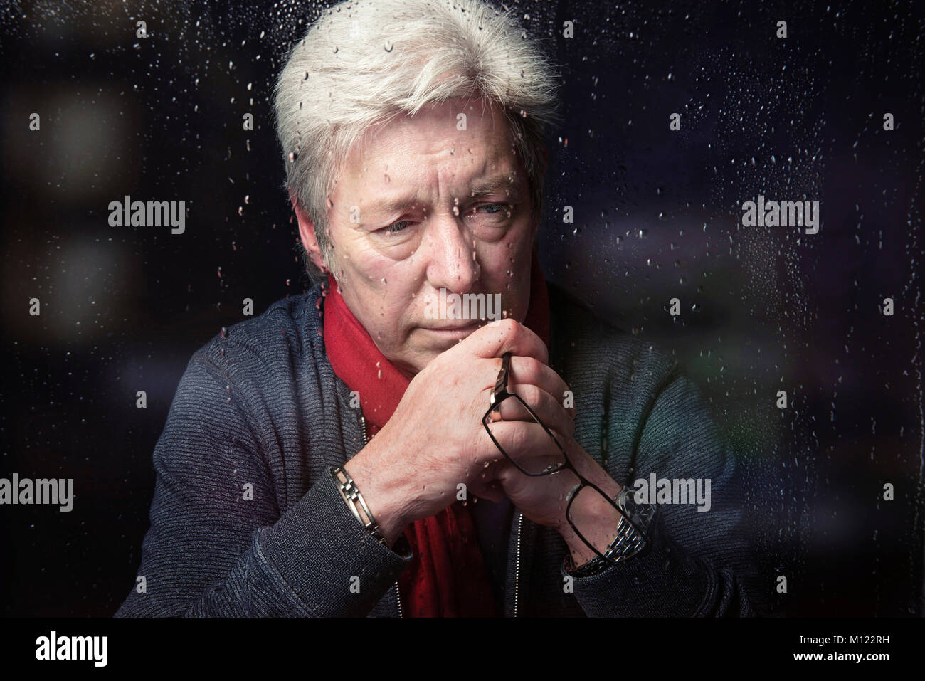 Depressed sad Man looking tearful holding glasses in front of face at window with rain drops close up head shot - Stock Image