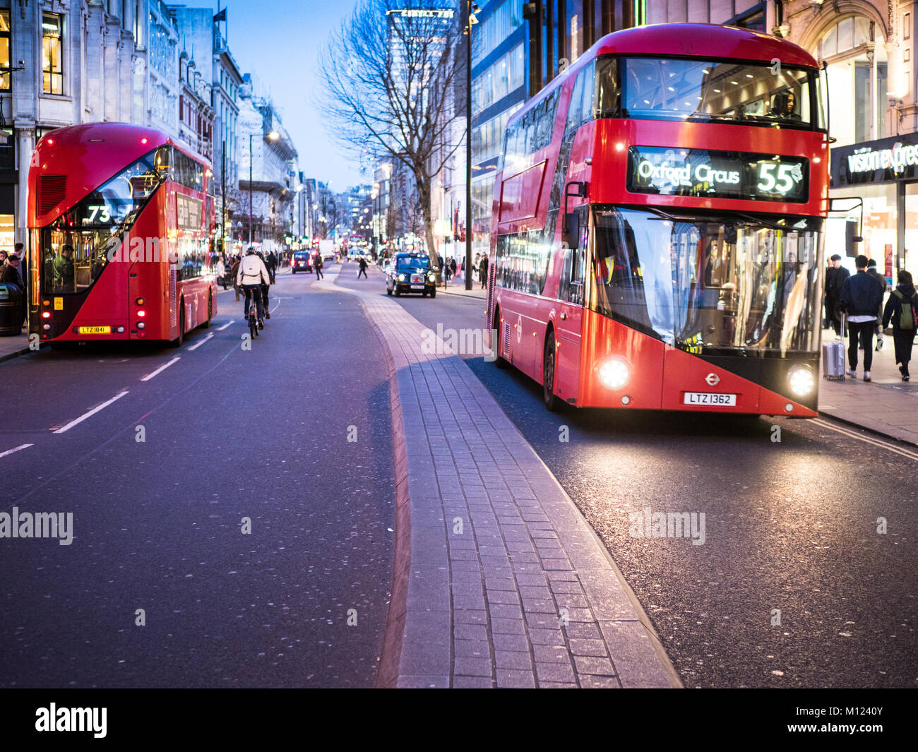 London Oxford Street Buses - two new Routemaster buses on Oxford St, Londons main shopping street at dusk - Stock Image