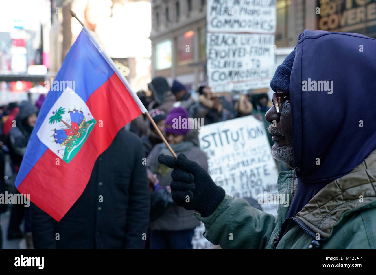 A protestor with a Haitian flag in a rally against racism and President Trump's disparaging comments about Haiti - Stock Image