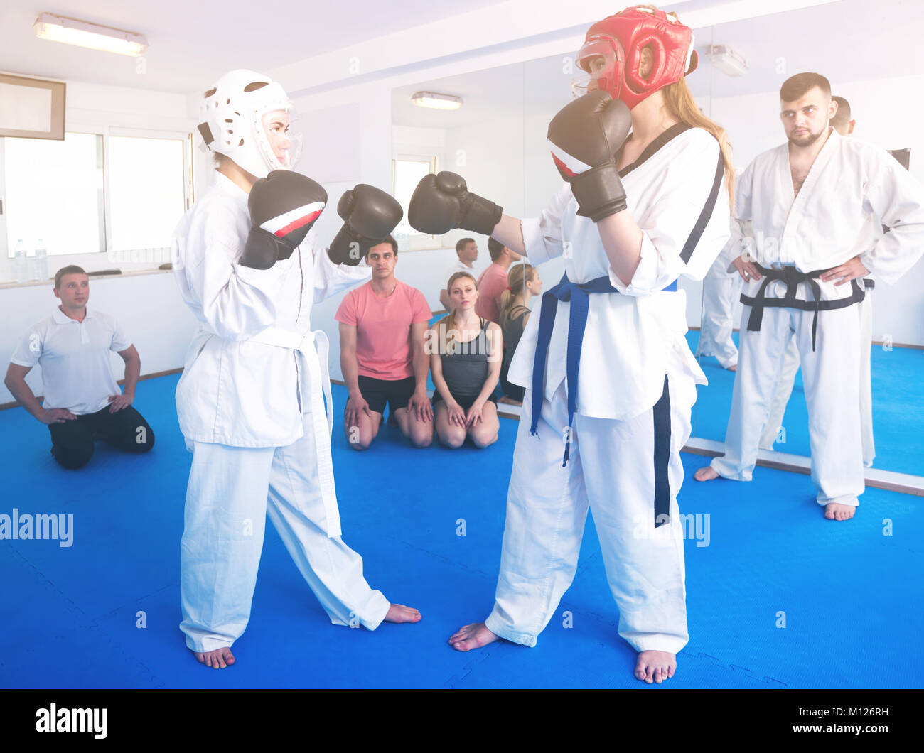 Female trainees conduct sparring for a taekwondo class Stock