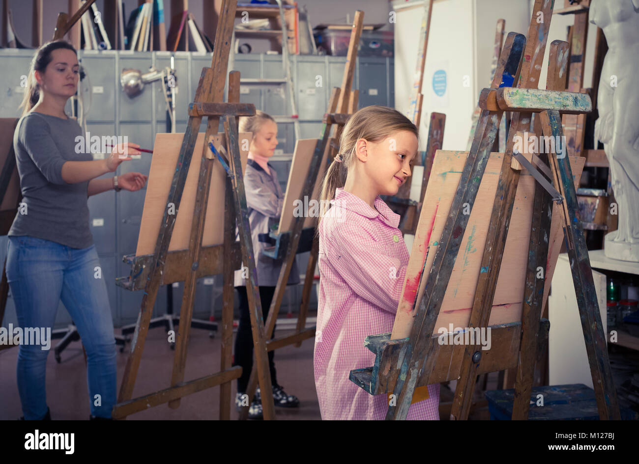 happy germany schoolgirls diligently training their painting skills during class at art studio - Stock Image