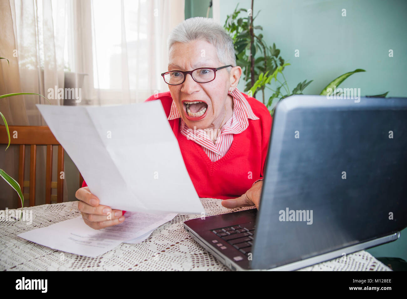 Senior woman outraged with bills from electricity company - Stock Image