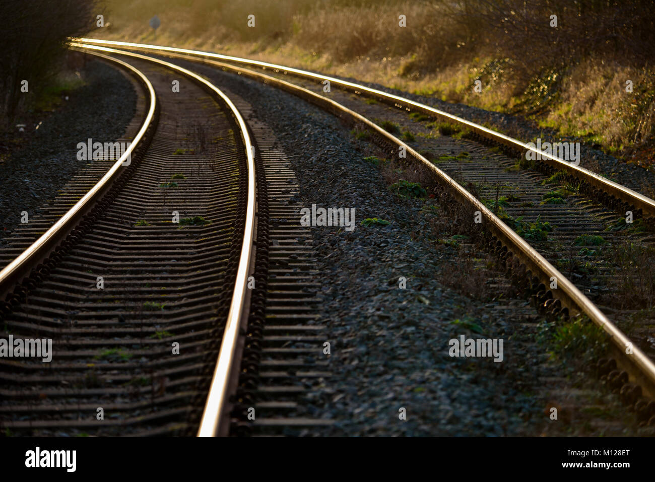 curved railway lines glinting in the evening golden sunshine - Stock Image