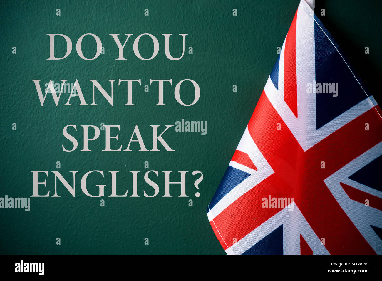a flag of the United Kingdom and the question do you want to speak English? against a dark green background Stock Photo
