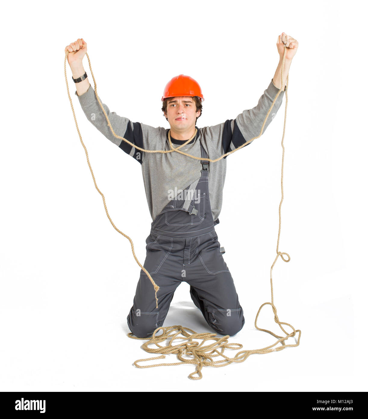 A young worker in grey uniform tied up with rope on white isolated background. - Stock Image