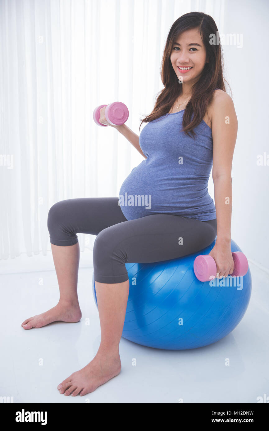 Pregnant Woman Doing Exercise With Yoga Ball Holding Barbell In Each Stock Photo Alamy