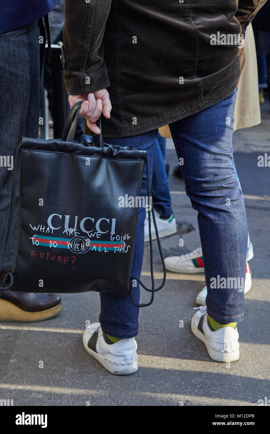 7ed7face44 MILAN - JANUARY 14: Man with black leather Gucci tote bag and blue ...
