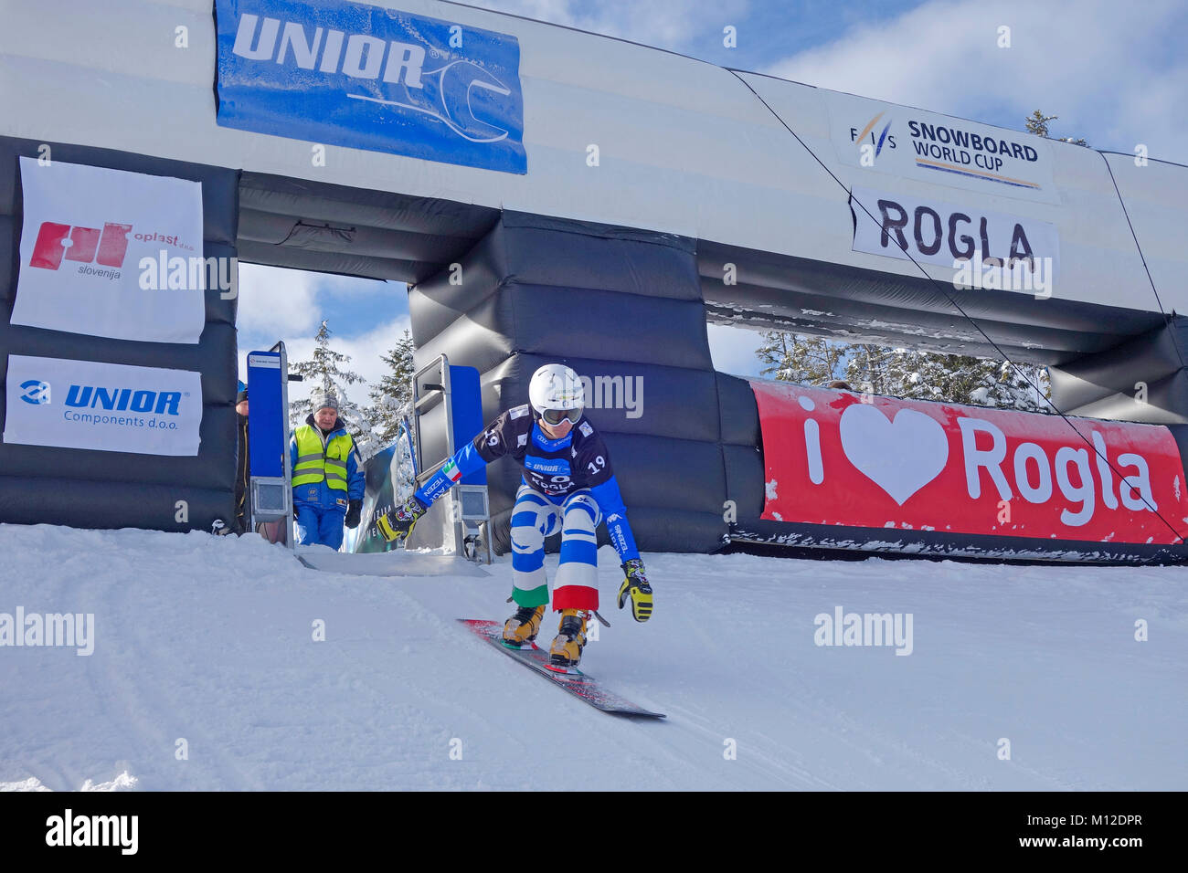 Snowboard competitor in parallel slalom has started  from the start gate. Rogla ski resort, Slovenia. - Stock Image