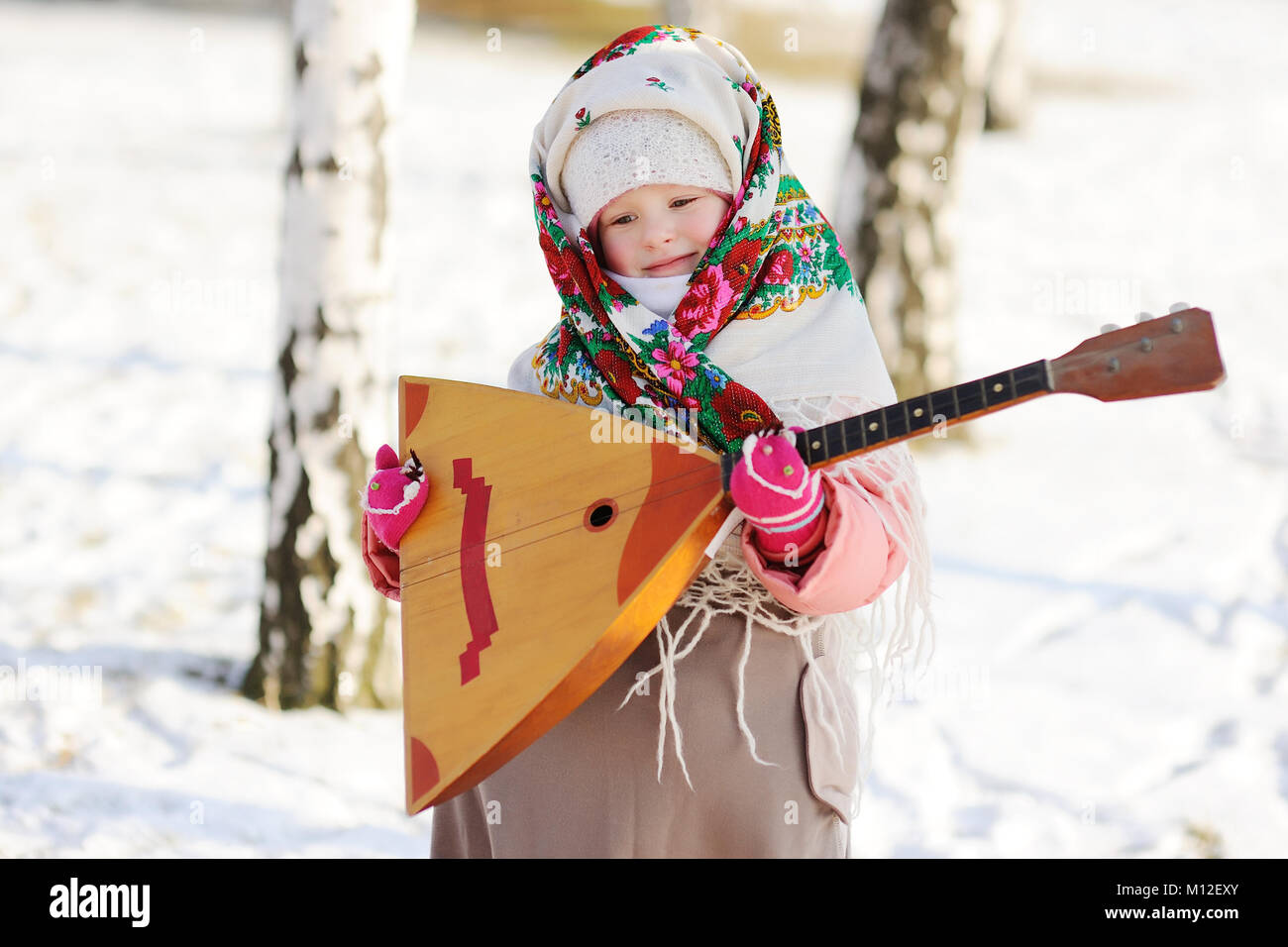 child girl in a fur coat and a scarf in Russian with a balalaika - Stock Image