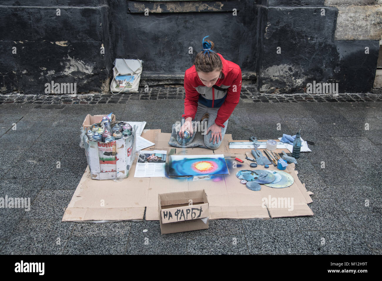 Lviv, Ukraine - January 21, 2018: Spray paint show, young beautiful sitting on the knees and drawing the picture, - Stock Image