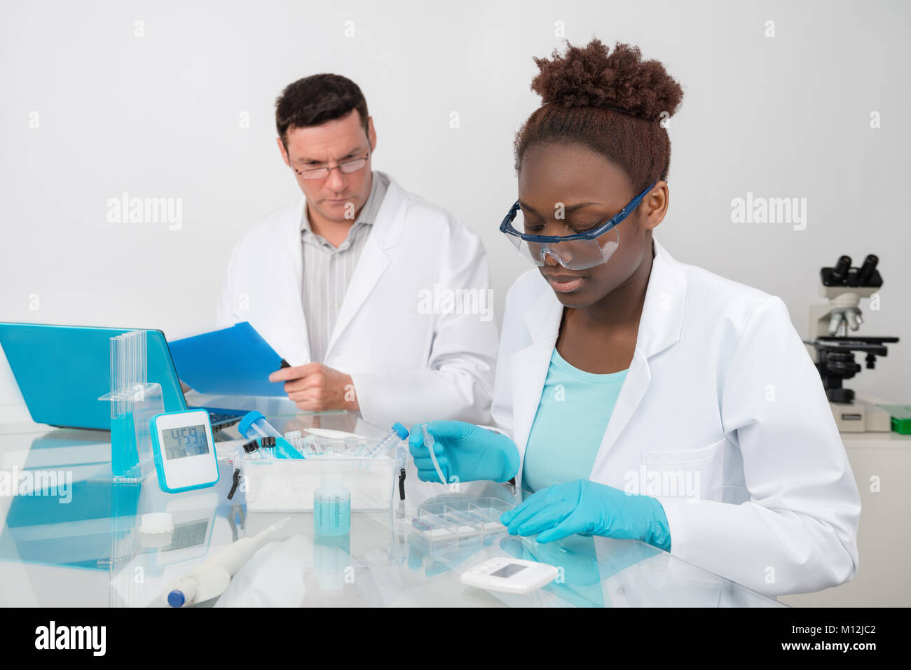 Scientists, male and female, work in research facility. Mature scientist supervises work of younger colleague. Focus - Stock Image
