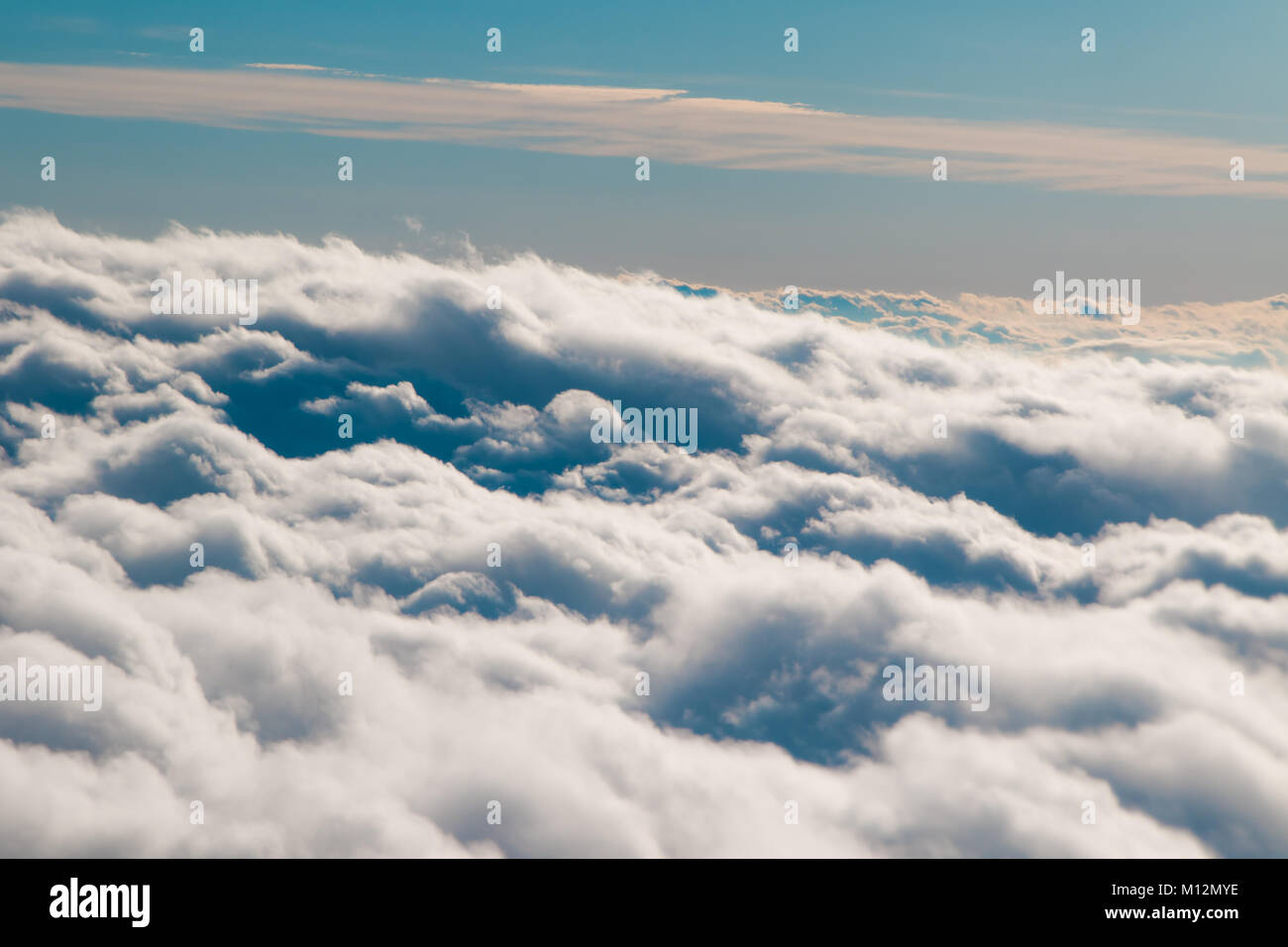 A wave of fluffy clouds roll by an airplane window - Stock Image