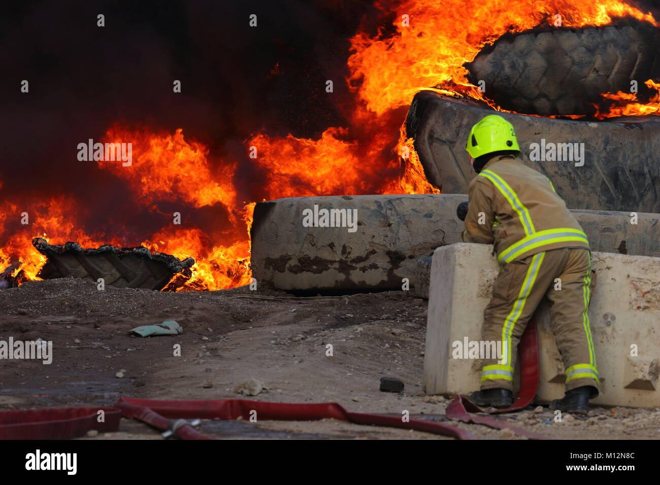 Fireman waiting for a water supply to his hose during a tyre fire in Beeston,Leeds. - Stock Image