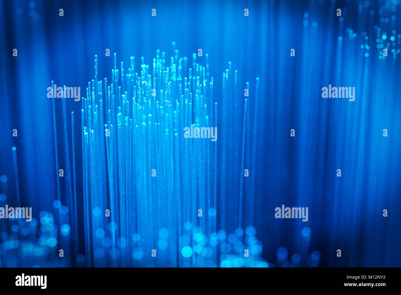 3d rendering of fiber optics against blue light background - Stock Image