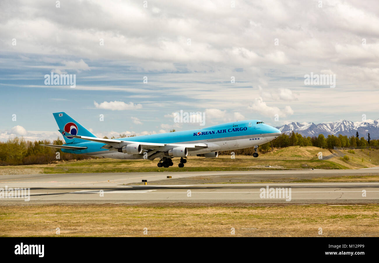 Korean Air Cargo jet landing at Ted Stevens Anchorage International Airport in Southcentral Alaska with the Chugach - Stock Image