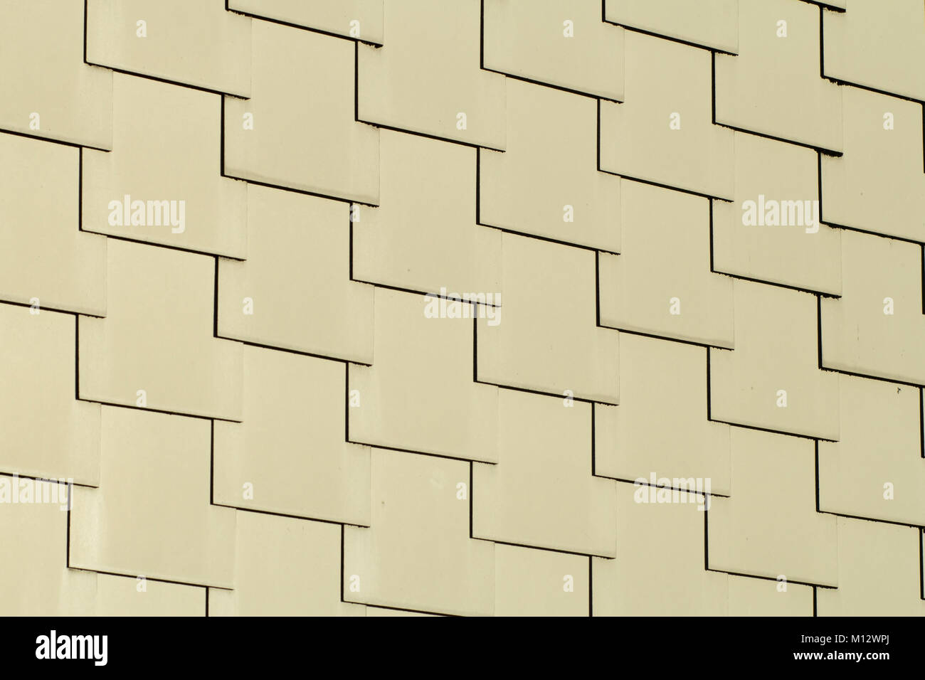Abstract architectural background of overlapping cream-colored rectangular tiles in repeat rows in a full frame - Stock Image