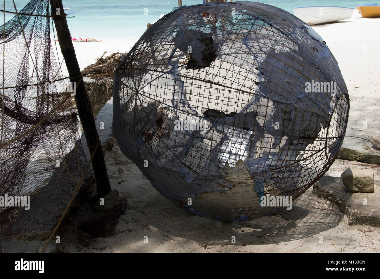 Metal sculpture of the world, the globe, laying on its side in the sun on Nungwi beach in Zanzibar, Tanzania with - Stock Image