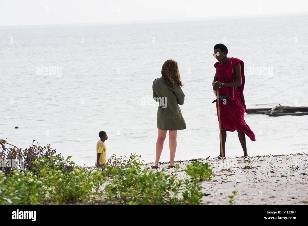 Massi man in traditional red cloak chats with a European woman on the beach in Jambiani Zanzibar Tanzania with a Stock Photo