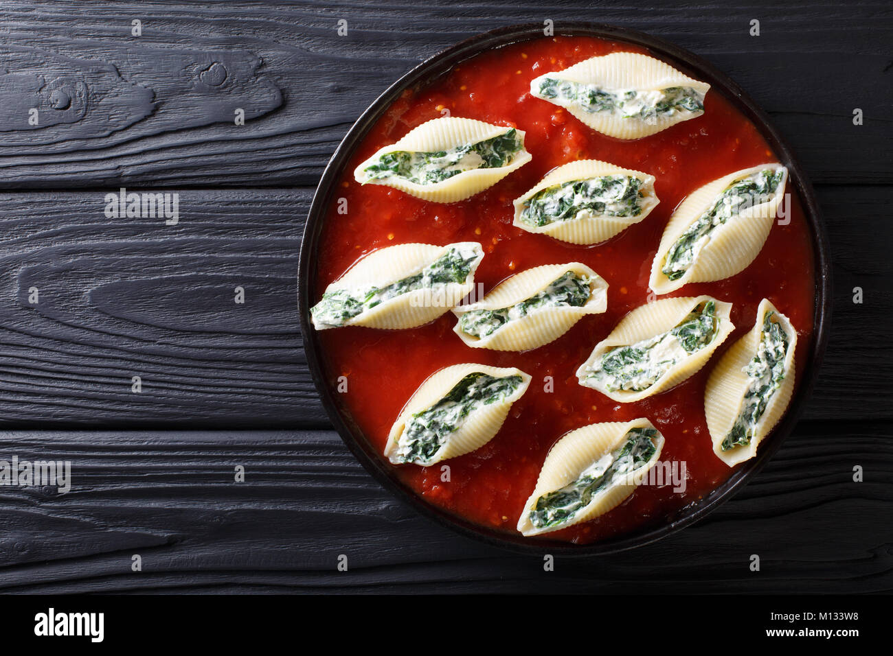 Shell pasta with spinach and cream cheese with tomato sauce closeup on a plate. horizontal top view from above Stock Photo