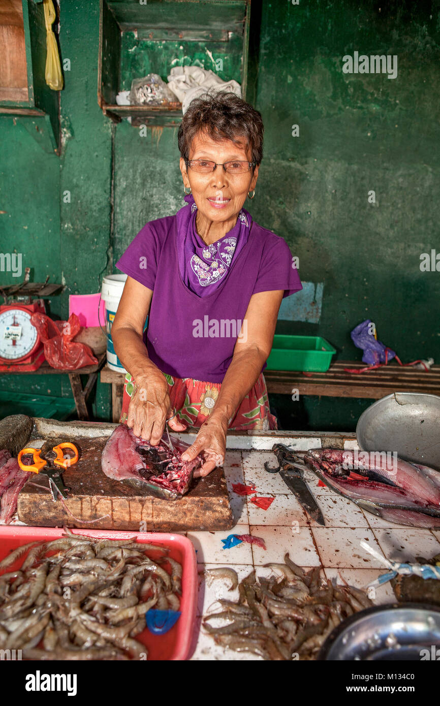 A senior age Filipino woman works in her fish stall splitting Bangus, a staple food fish, in the market at  Barretto, - Stock Image