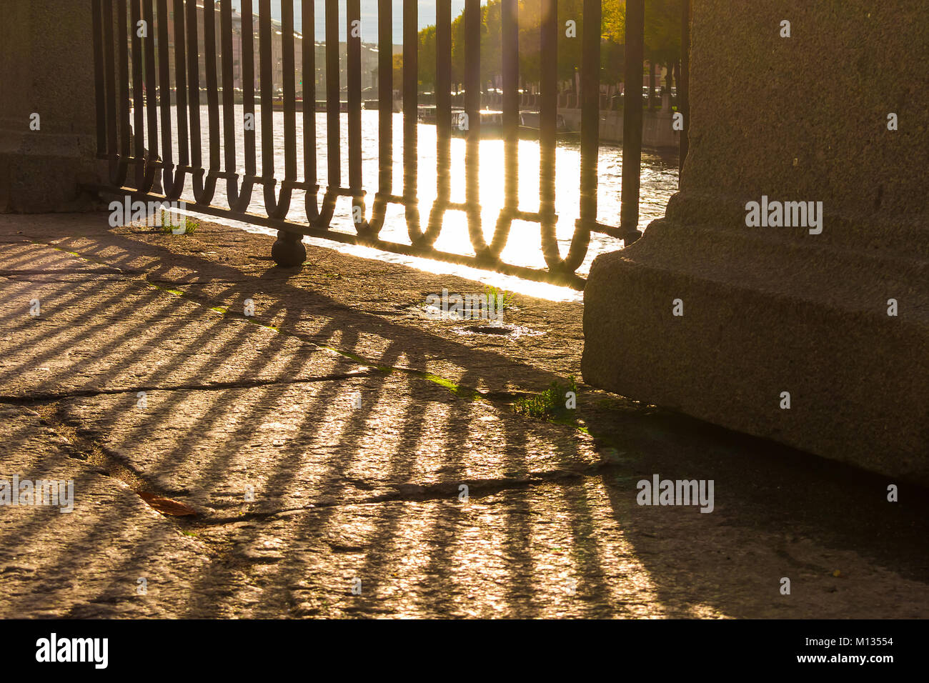 A grate of the fence of the granite embankment and its shadow on the pavement closeup in sunny day, Saint Petersburg, - Stock Image