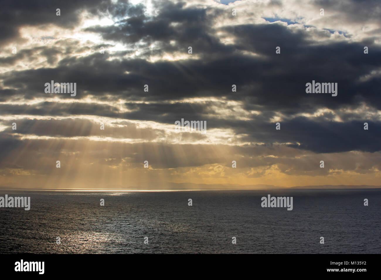 Sunrays bursting through dense sheet of rain clouds over sea water at sunset - Stock Image