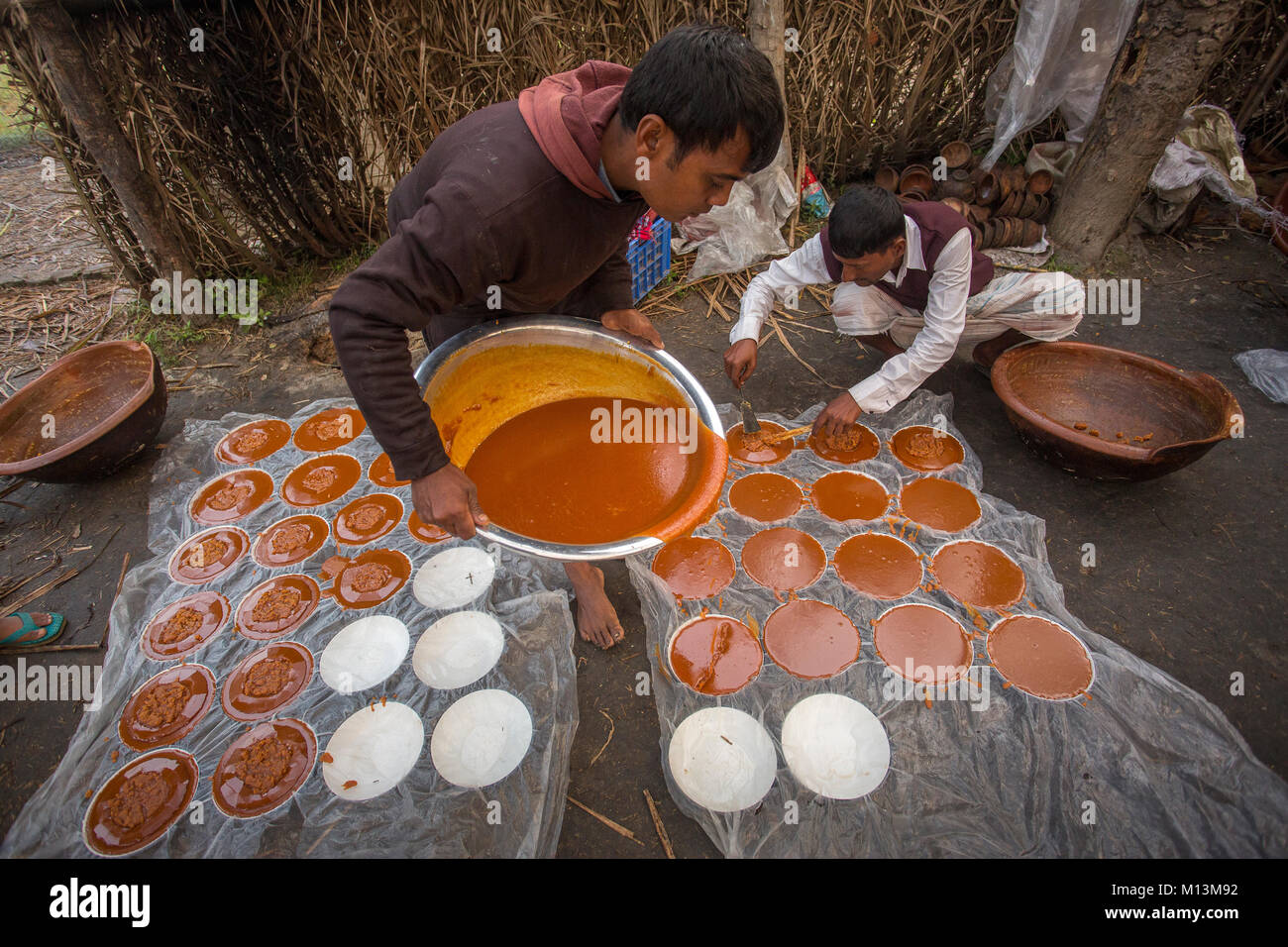 Boiled hot Date Palm Tree juice is being poured into the container at Iswardi, Bangladesh. - Stock Image