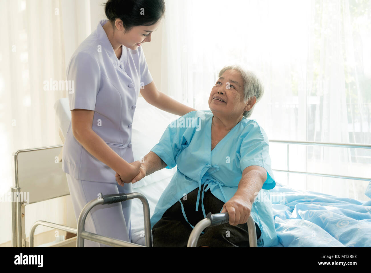 Asian young nurse supporting elderly patient disabled woman in using walker in hospital. Elderly patient care concept. - Stock Image