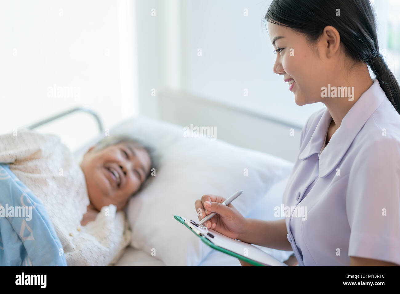 Asian nurse checking up the history of the disease elderly patient lying in bed. Nurse cares for a elderly woman. - Stock Image